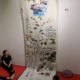 Lange Papierbahn mit Schrift und Fotos hängt von der Decke.