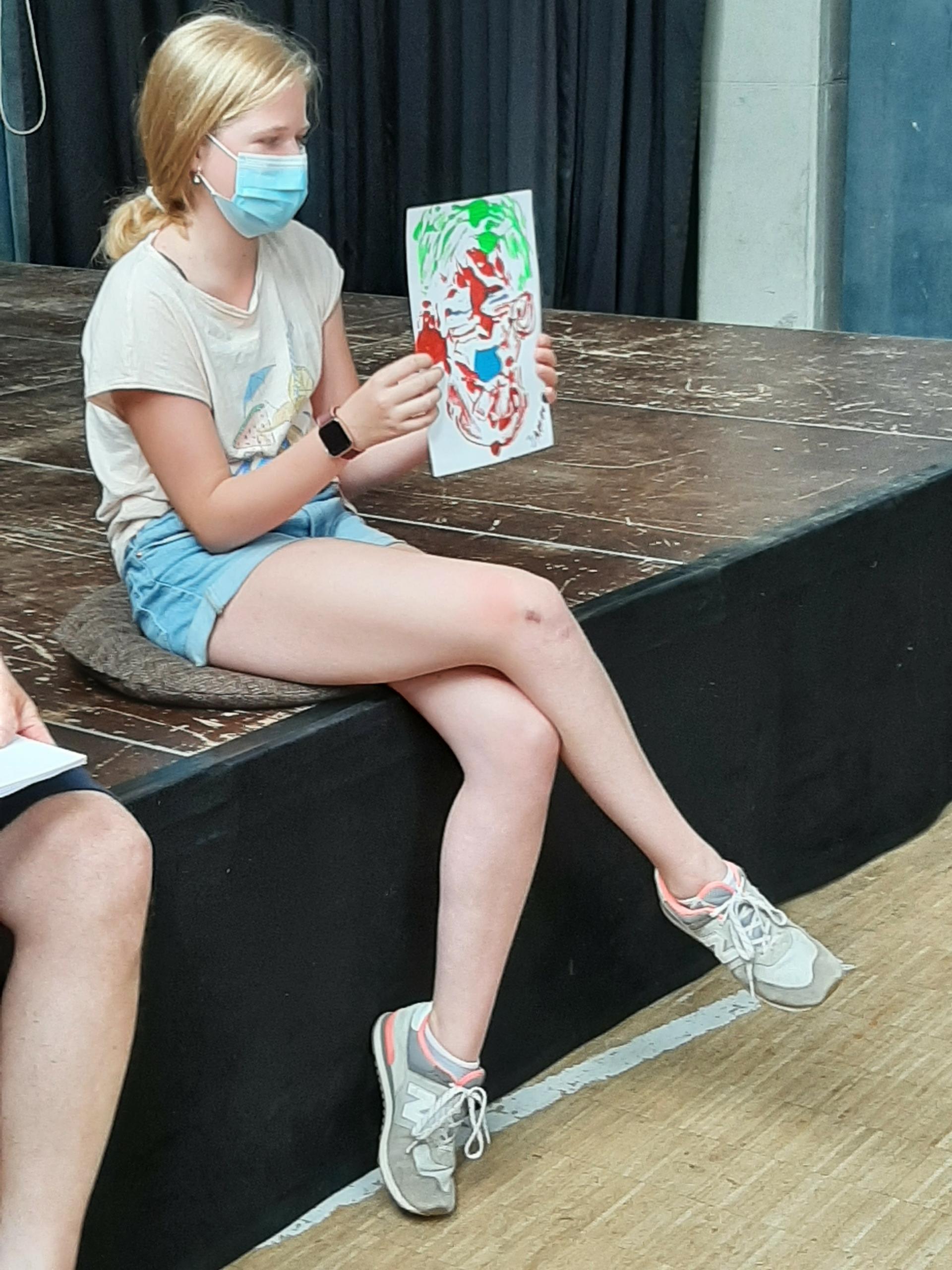 Farbiges Porträt in der Hand eines Mädchens auf der Bühne